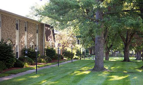 the exterior of a stone-walled apartment building with a freshly mowed lawn and many large trees on the property